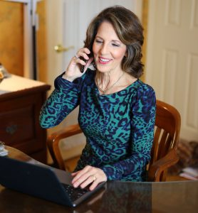Dietitian Speaker Bonnie Taub-Dix sits at her home office desk about to give a video presentation. She is wearing a green and blue long-sleeved dress.