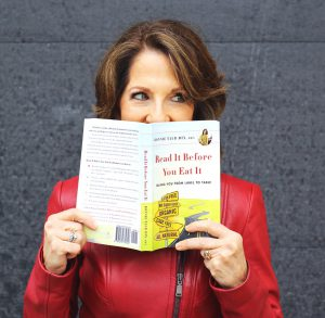 """Dietitian Speaker Bonnie Taub-Dix peeks mischievously over the top of her book, """"Read It Before You Eat It."""" She wears a red leather jacket with a zipper."""