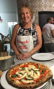 Dietitian Speaker Paula Quatromoni stands in an apron behind a pizza she crafted during an Italian cooking class.