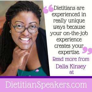 Dietitian Speaker Dalia Kinsey is ready to present, in a green shirt with black jacket, glasses, and a big smile.