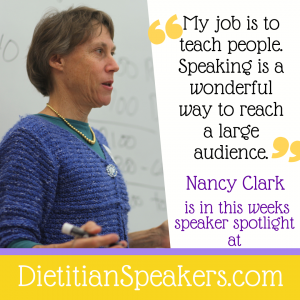 Dietitian Speaker Nancy Clark presents in front of a white board with a marker in her hand. She wears a blue top and necklace and is presenting on sports nutrition.