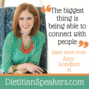Dietitian Speaker Amy Goodson leans forward in her chair as if to share something special with her audience. She's wearing a green patterned top and a bright orange necklace, plus a big smile.